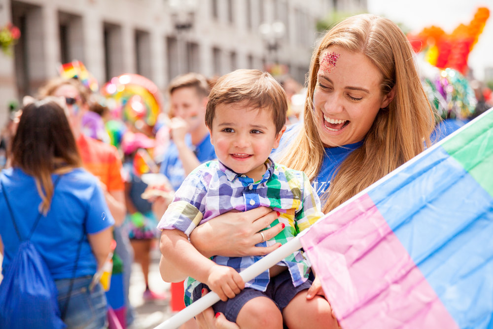 Hélène Vincent holds a child while he holds a LGBQT pride flag during his first Boston Pride Parade event.