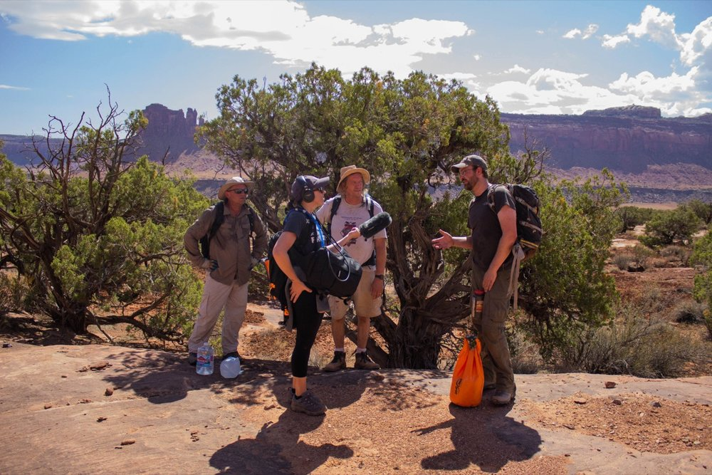Four people in the desert surrounded by mountains stand next to each other in hiking gear. one of them is wearing headphones and is pointing a mic at a talking man