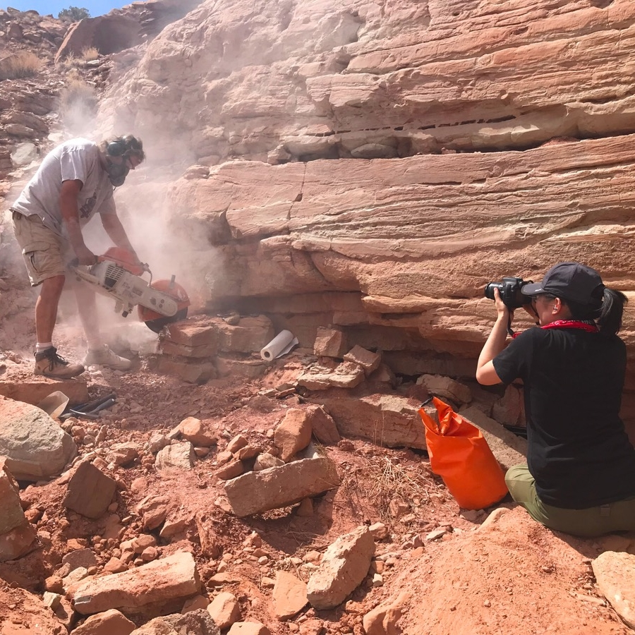 A man, wearing safety glasses, headphones, and a mask, is blade-sawing through rock, causing dust to rise, while a woman off to his right, is filming the process