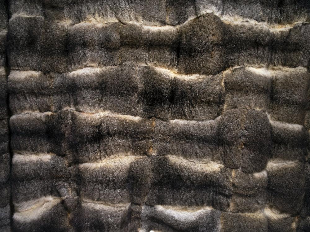 Carol McGregor,   Wathaurung and Scottish     Skin Country  2018  Possum skins, charcoal, ochre, binder medium, waxed thread  (detail)  photo by Markus Ravik