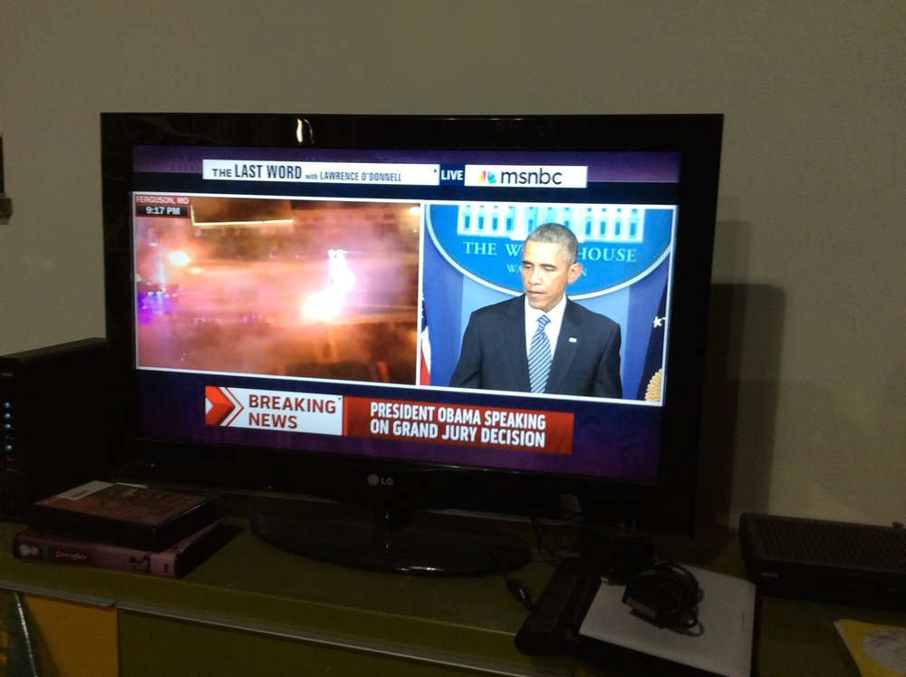Split screen from MSNBC during the start of the uprisings in Ferguson, Missouri, 24 November 2014