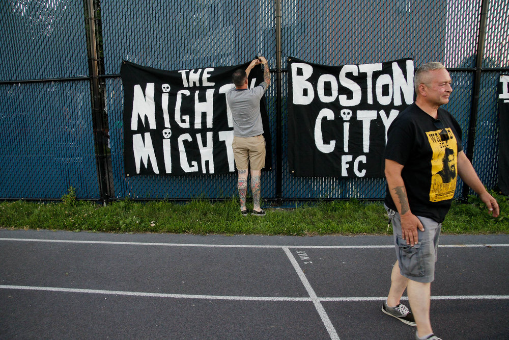 Members of the Ironsides Crew take down their banners following Boston City FC's victory. (c) Burt Granofsky