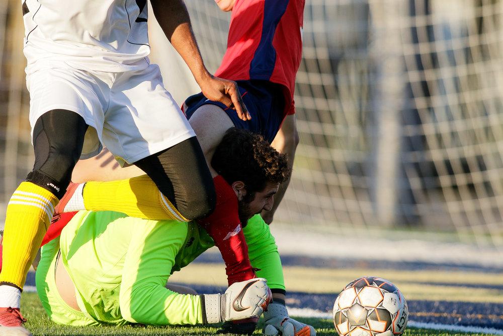 Boston City FC goalkeeper Jacob Wagmeister finds himself tangled up as he tries to retrieve the ball. (c) Burt Granofsky