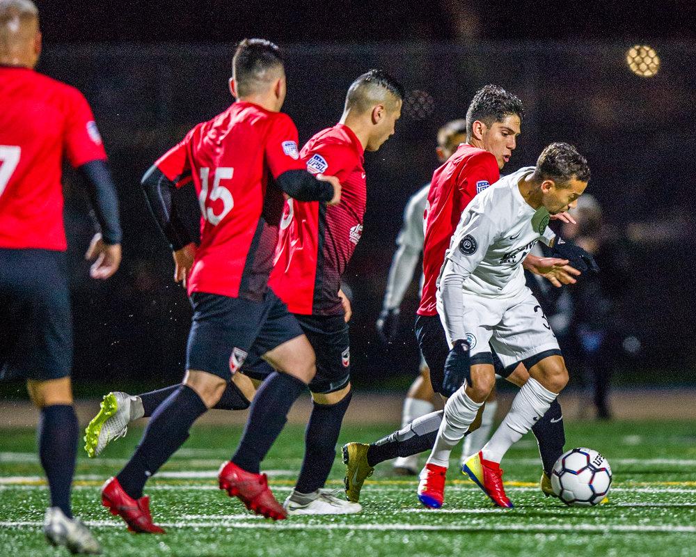Cal Utd FC vs Inocentes_Paolo Cardozo fighting through the red wall.jpg