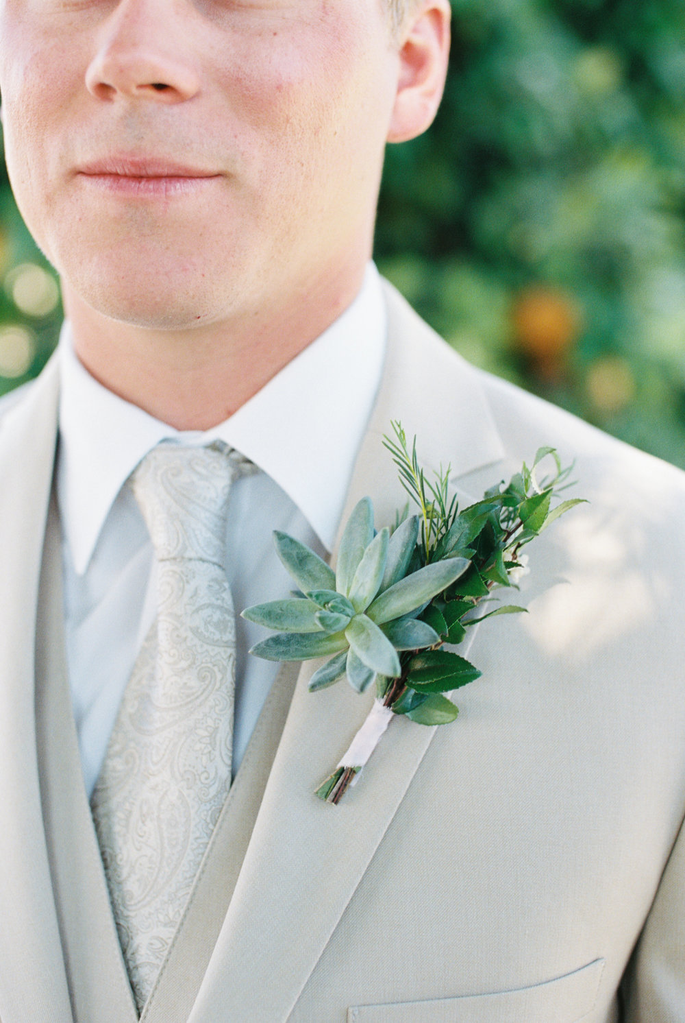 Dairy Farm Wedding - Succulent Boutonniere and Groom in tan suit