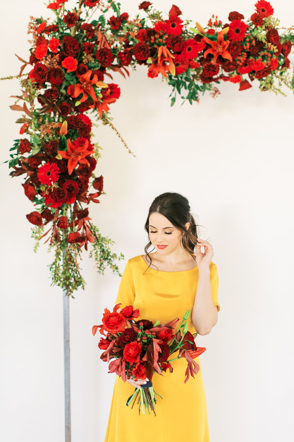 red and yellow wedding inspiration - red flower arch ceremony inspiration