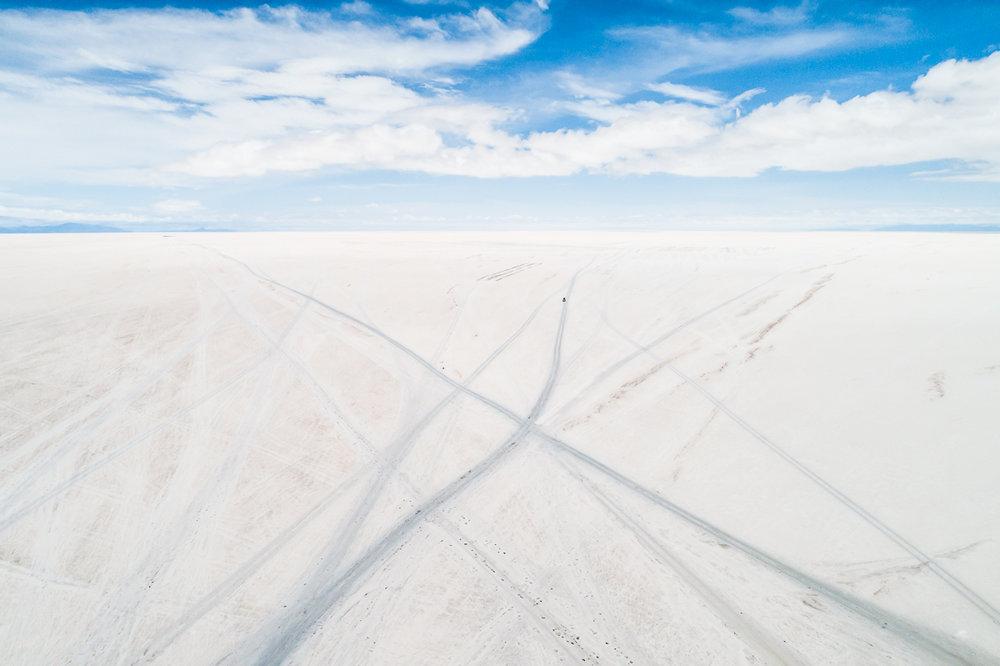 blue-white-salar-de-uyuni-salt-flats-potosi-bolivia-car-tracks-vast-expanse-desert-vastness-jeep-4x4-wheel-drive-road-roadtrip-south-america.jpg