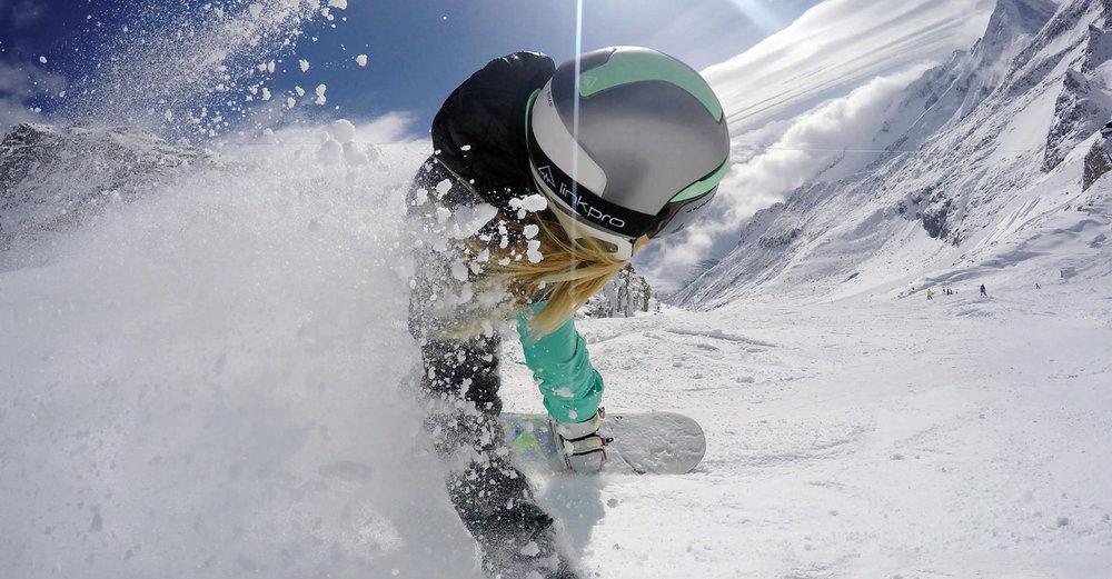 Link Pro - Curventa - In situ - snowboard - helmet - communication - headphones - silver helmet  - action shot - female snowboarder - carving - mountain