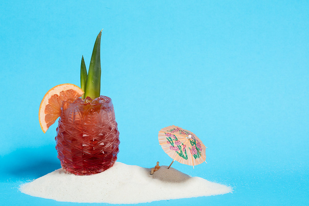 Amity Island cocktail in pineapple glass with decorative umbrella