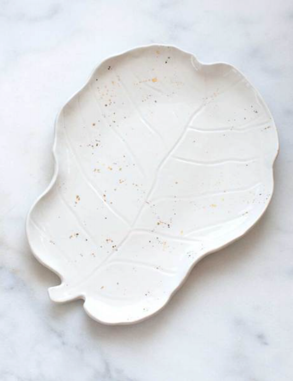 Picture it: Every time your art-lover arranges a cheese platter their guests oooh & ahhh over this beautiful, handmade, porcelain & gold fiddle leaf fig platter! Your art-lover then gets to tell their guests all about the North Carolina based artist behind the handmade porcelain platter, Lindsay Emery, and how she took her inspiration from the centuries old traditional of cabbage and lettuce ware to create a modern version based on the most ubiquitous-to-our-moment leaf, the Fiddle Leaf Fig!  The platter is luxury at its finest. Hand shaped from dense porcelain for an ideal serving heft, with a serving surface that is glazed with a translucent, high-gloss ivory white glaze & finished with celebratory gold splatters!  The best part will be when you show your art-lover the underside, which is signed by Lindsay Emery herself and sanded to a smooth finish! ($116)