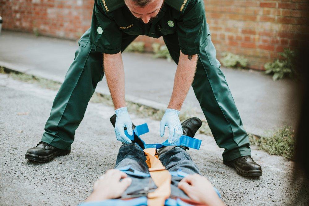 car accident paramedic helping man