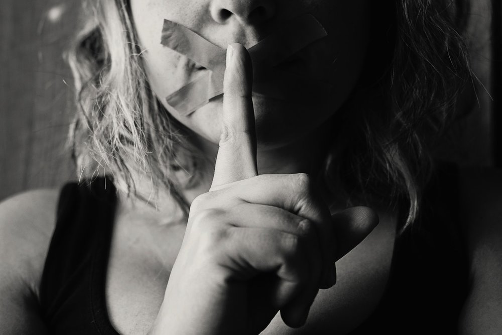 tape on the mouth and someone with finger in front of month- be quite symbol