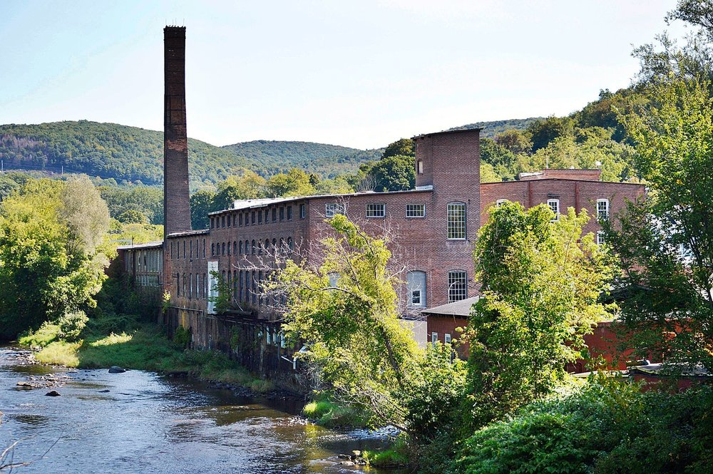 The Union Mill, center, and Eagle Mill buildings will be renovated as part of the Mill Renaissance plan to redevelop the former Eagle Mill in Lee. The smokestack, seen as a symbol of the town's once dominant paper industry, will be preserved.