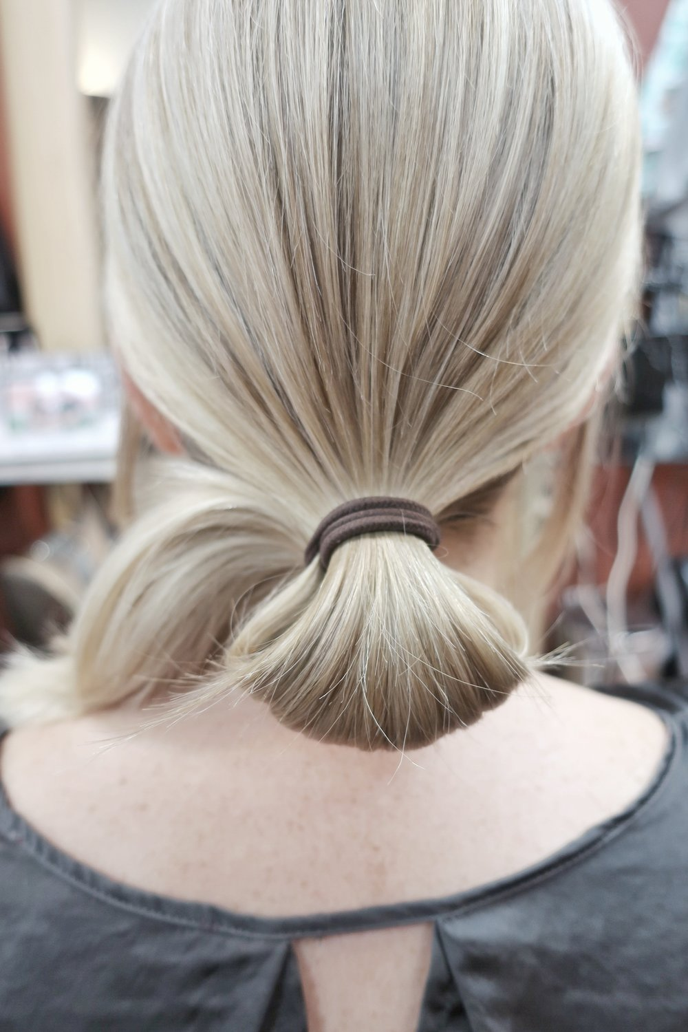 Tie hair with hair tie and when wrapping the last time leave hair into a bun like photo