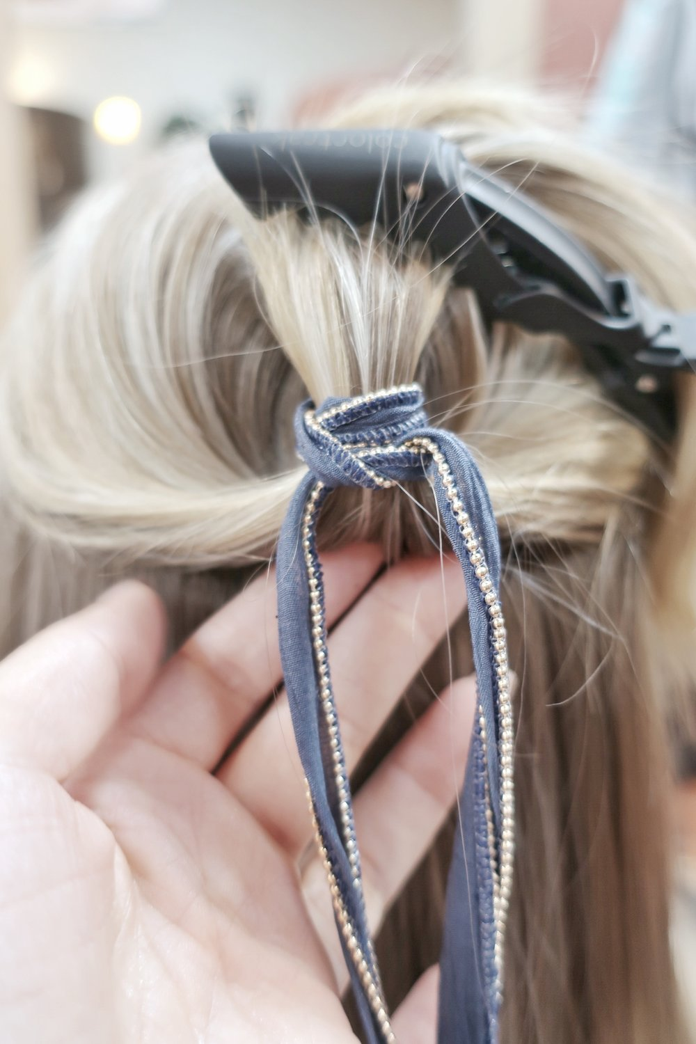 Now take your detail piece and start by wrapping around and tying a knot in the back to hide knot. Continue to wrap around the hair until reaching desired length. Secure with knot in the back and tuck extra fabric.