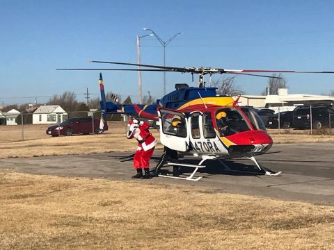 Santa arrives to the Northside Toy Drive Toy Giveaway in a helicopter courtesy of Rico Aviation.