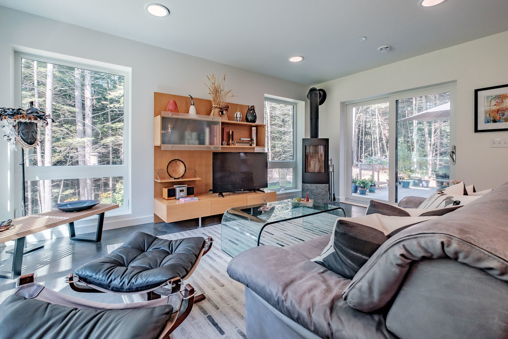 Interior of Kelsey Brook's newest home—designed by Mottram Architecture— showing the Tula wood stove that was central to its design. Triple pane windows face west to o'er shading from the summer sun and sit just above the floor, giving the appearance of being connected to the woods beyond. Photo: Michael Eric Berube