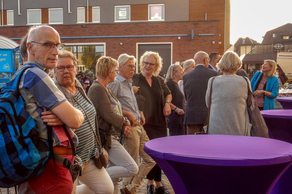 Veel leden van Fotoclub Salland en winkelend publiek wonen de onthulling bij.