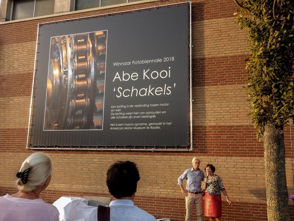 Diny Heidenrijk, voorzitter van Fotoclub Salland spreekt de winnaar Abe Kooi toe.
