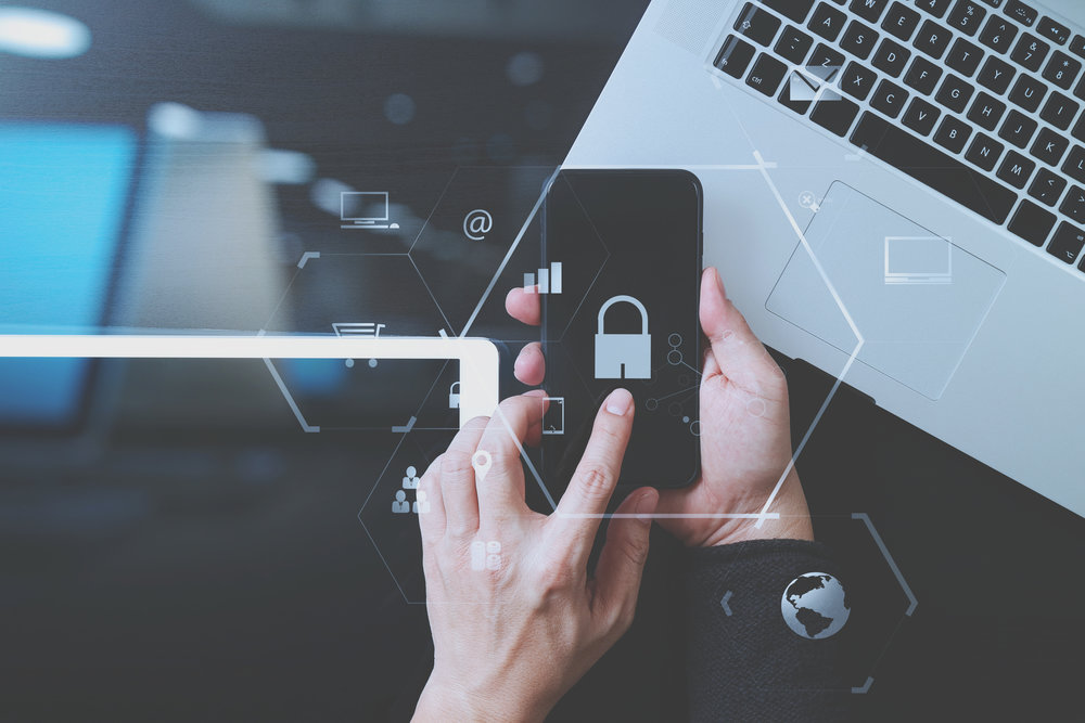 cyber security internet and networking concept.Businessman hand working with VR screen padlock icon mobile phone on laptop computer and digital tablet