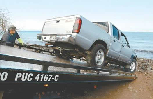 """808 Towing winches a Nissan Frontier onto the bed of their tow truck near an area known as Cut Mountain on the west side. The truck had rolled down the beach into the ocean"" Photo By Matthew Thayer"