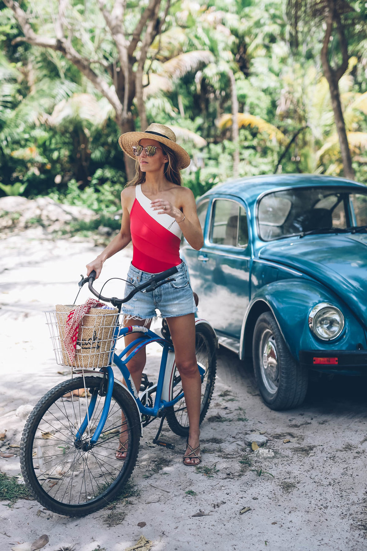 Jess-Ann-Kirby-summersalt-one-shoulder-swimsuit-levis-cut-off-shorts-straw-panama-hat-Tulum-bike-ride-1.jpg