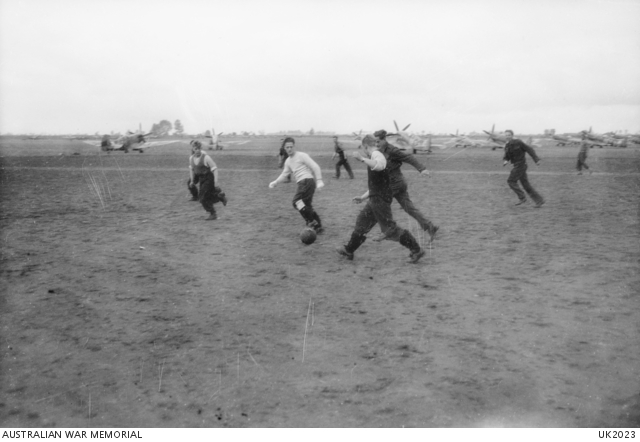 HOLLAND. 1944-10-23. RAAF AND RAF AIR AND GROUND CREWS OF SPITFIRE NO. 130 SQUADRON RAF KEEP WARM WITH A GAME OF SOCCER DURING A LULL IN OPERATIONS AT AN AIRFIELD IN HOLLAND. -