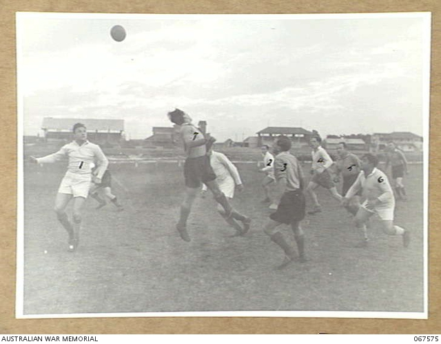 - MASCOT, NEW SOUTH WALES, AUSTRALIA. 1944-07-13. PERSONNEL OF THE 2ND EMPLOYMENT COMPANY AND THE 3RD EMPLOYMENT COMPANY ENJOYING A GAME OF SOCCER ON ASCOT RACECOURSE. IDENTIFIED PERSONNEL ARE:- N321039 PRIVATE SIFE, 2ND EMPLOYMENT COMPANY (1); N256915 PRIVATE B. RUMM, 2ND EMPLOYMENT COMPANY (2); N385846 PRIVATE H. BLOOD, CAPTAIN, 3RD EMPLOYMENT COMPANY (3); N224965 PRIVATE W. BENDIT, 2ND EMPLOYMENT COMPANY (4); N463189 PRIVATE F. WEISS, 3RD EMPLOYMENT COMPANY (5); N224777 PRIVATE D. GIUFFRE, 2ND EMPLOYMENT COMPANY (6); N321036 PRIVATE P. MAY, 3RD EMPLOYMENT COMPANY (7).