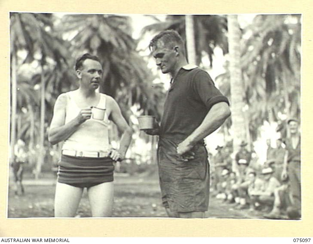 - MILILAT, NEW GUINEA. 1944-08-06. TWO STAR PLAYERS IN THE SOCCER MATCH BETWEEN TEAMS FROM HEADQUARTERS, 5TH DIVISION AND THE 4TH INFANTRY BRIGADE ENJOY A DRINK AT HALF TIME DURING THEIR GAME ON THE NEW HEADQUARTERS SPORTS OVAL. THEY ARE:- B419 SENIOR REPRESENTATIVE R.G. SCOTT, AUSTRALIAN RED CROSS SOCIETY, WHO PLAYED WITH THE SOUTH ADELAIDE TEAM AND REPRESENTED SOUTH AUSTRALIA (1); NX120887 CORPORAL M.R. WYNN, PLAYED WITH METTERS TEAM, SYDNEY AND WAS AN AUSTRALIAN REPRESENTATIVE IN SEVERAL INTERNATIONAL SERIES (2).