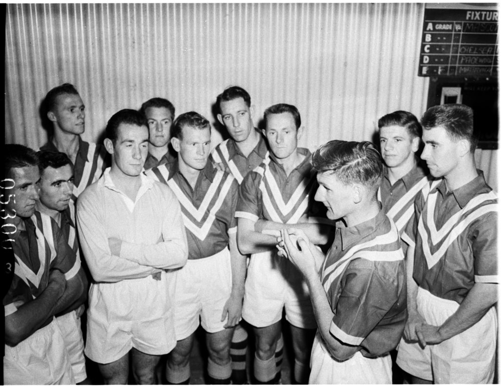 Australian captain Joe Marston has a few words with his team before taking on English visitors Blackpool FC - 1958 - (TROVE)