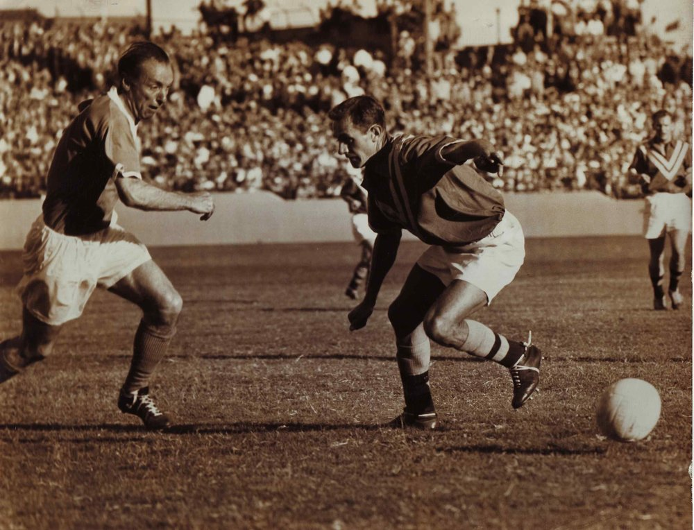 English great sir Stanley Matthews takes on Australian captain Joe Marston at the Sydney Sports Ground during Blackpool's tour of Australia in 1958. - (TROVE)