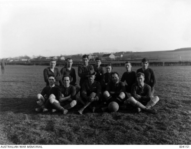 An outdoors group portrait of the Commanding Officer Lieutenant Colonel William Reginald Ffrench DSO MC and unidentified members of the soccer football team of the 1st Australian Machine Gun Battalion sitting on a field. - Belgium: Wallonie, Namur, RouxFirst World War, 1914-1918