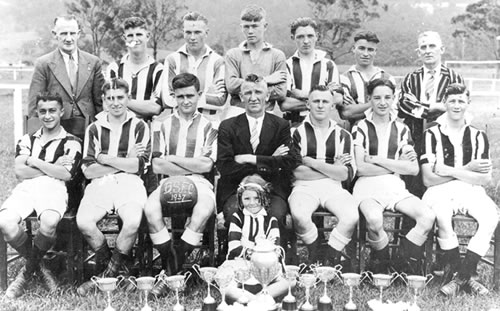 "1937-Balgownie Rangers - Back Row.James ""Judy"" Masters, Ronald McKinnon, Louis Johnston, Alan Hogarth, Stuart Keenan, Garfield Wills, Edward Parker (Med.)2nd Row: Joe Dalsanto, Angelo Bianchetto, Robert Barwise, Richard Johnston (Man.), Harry Johnston, James Keenan, Norman TolsonFront Row: Judy Masters (Mascot)(Balgownie Rangers)"