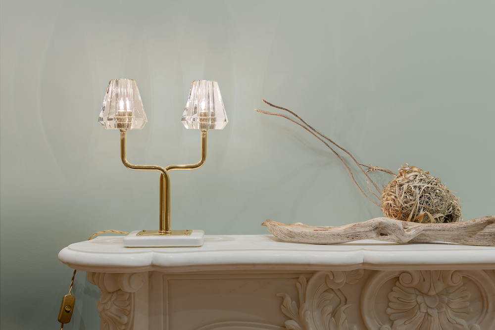 The  Aquiline Twin Stem Table Lamp  brings an elegant warm light to a hallway console or tall side table. Seen here against a bold Fromental wallcovering.