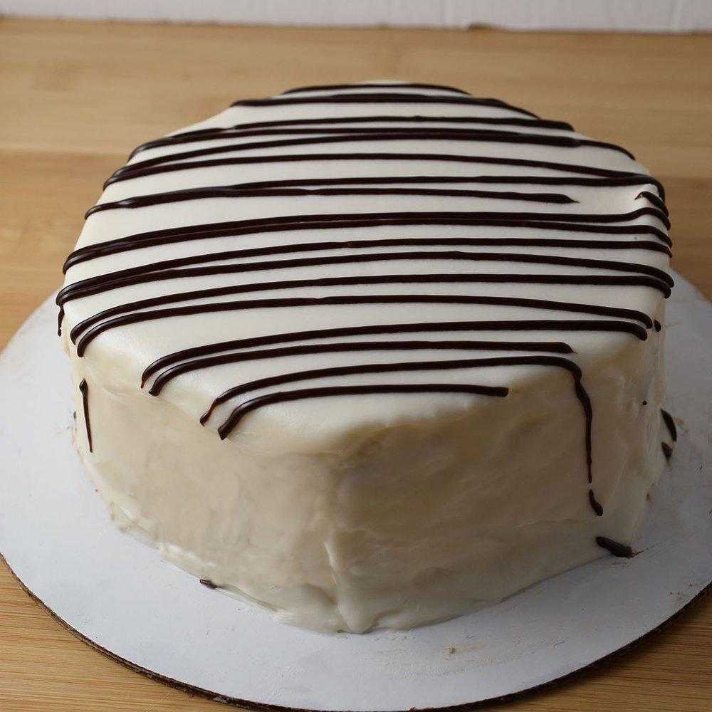 zebra Cake - Do you remember the mini zebra cakes you'd take for your school lunch? Well, we make a giant one. We also make mini ones, but now you can share. Vanilla cake, vanilla frosting, and white chocolate ganache.