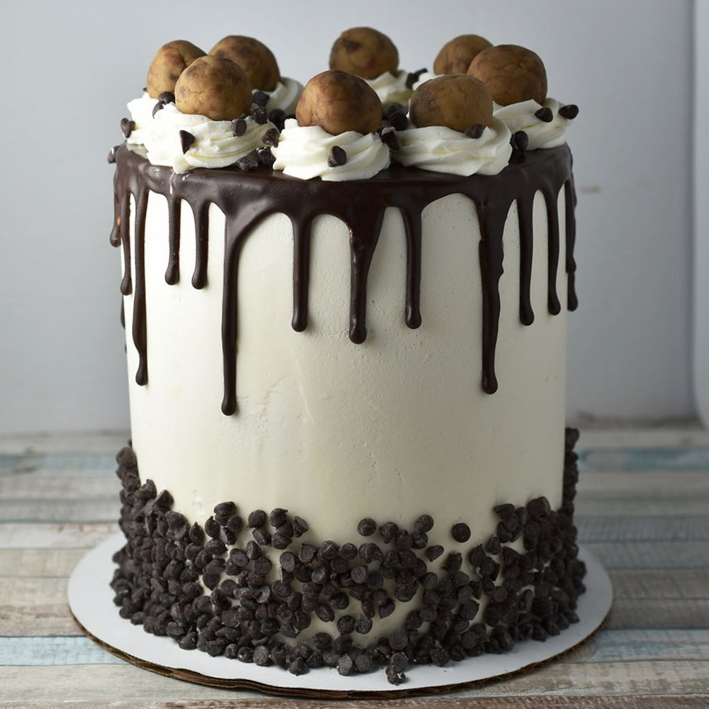 Chocolate Cookie DOugh - Another fun cookie dough cake! This one is chocolate layers with everyone's favorite chocolate chip cookie dough in the center! Vanilla frosting, mini chocolate chips, and ganache make it complete.