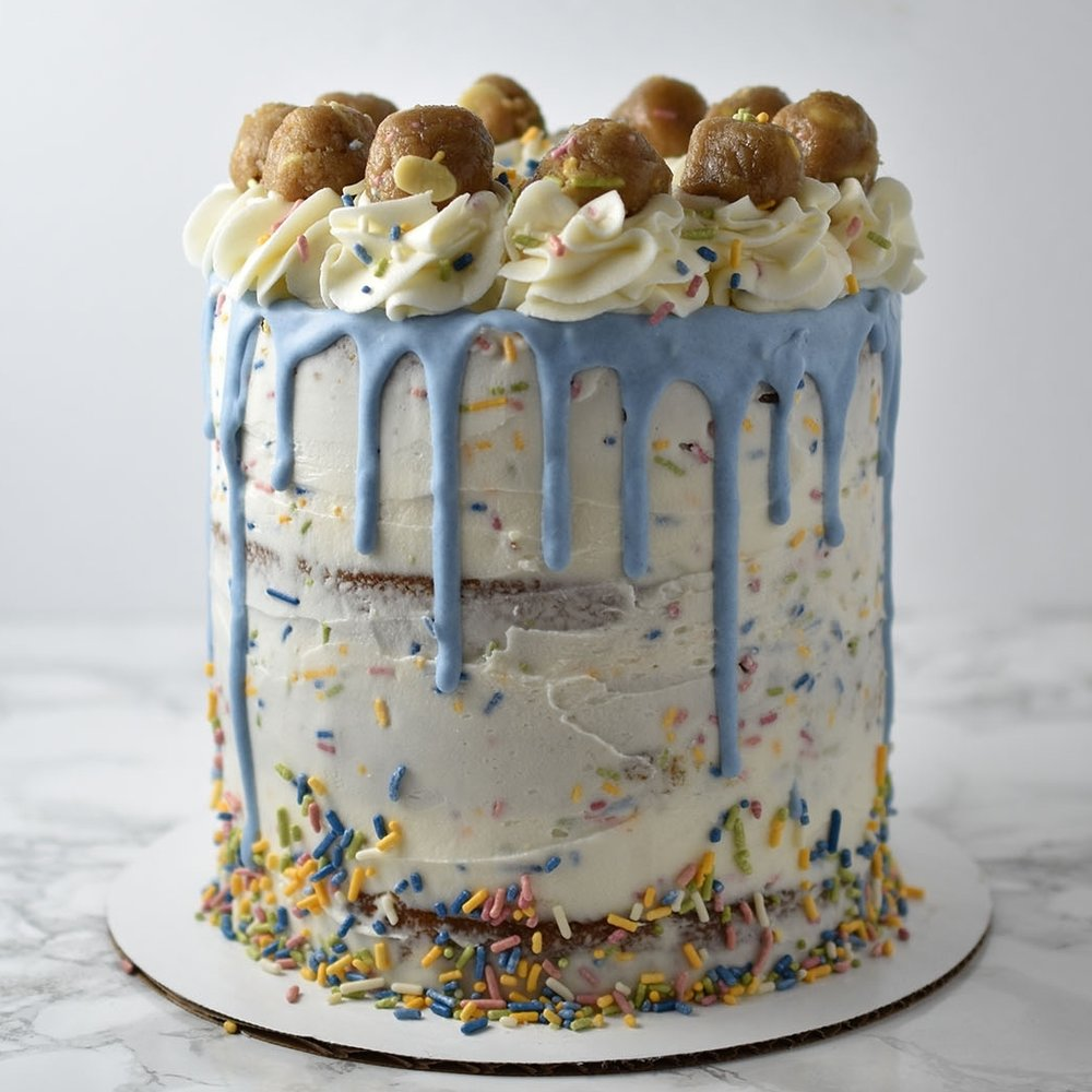 Confetti Cookie Dough - If this cake doesn't make you drool, than I don't know what will. Vanilla cake layers, Confetti white chocolate cookie dough filling, and confetti frosting. You can have it frosted semi-naked like the image above or frosted traditionally.