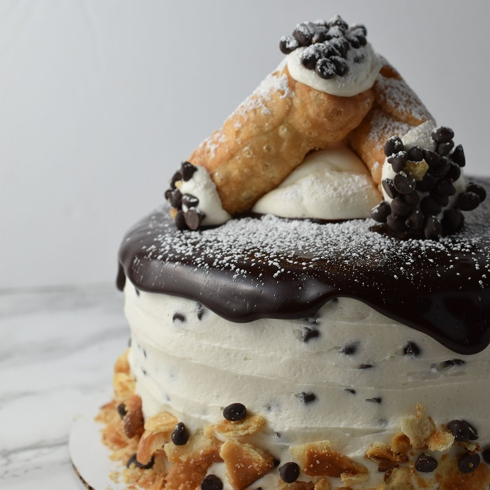 Cannoli - One of our most popular cakes is this tasty cannoli cake. It is made up of vanilla cake layers and chocolate chip cannoli cream frosting. It is topped with rich ganache and homemade petite cannolis.
