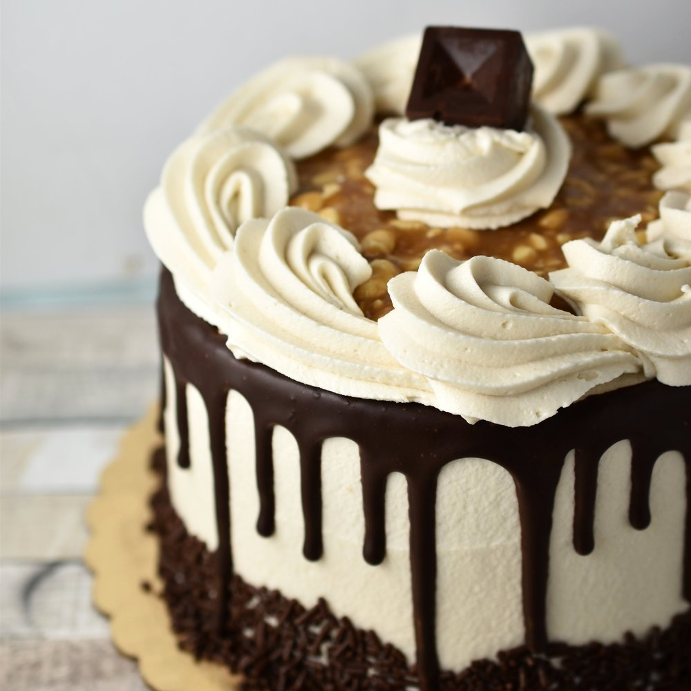 Snickers - Everyone loves Snickers! We just had to make a cake inspired by the tasty candy bar. Layers of chocolate cake filled with a homemade caramel and peanut mixture, finished off with caramel frosting and ganache.Gluten Free option available