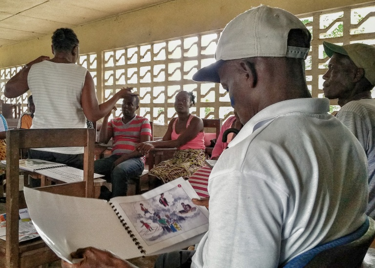 A participant reads through the Another Option Peer Education Guide during a community training.