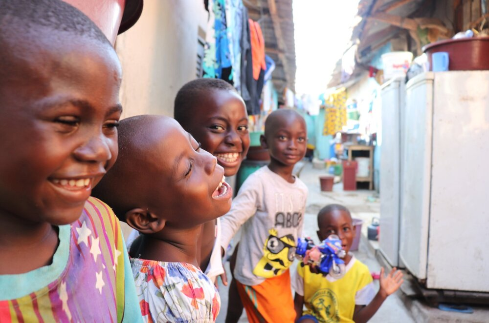 School-age children in Côte d'Ivoire laughing and playing near their house.