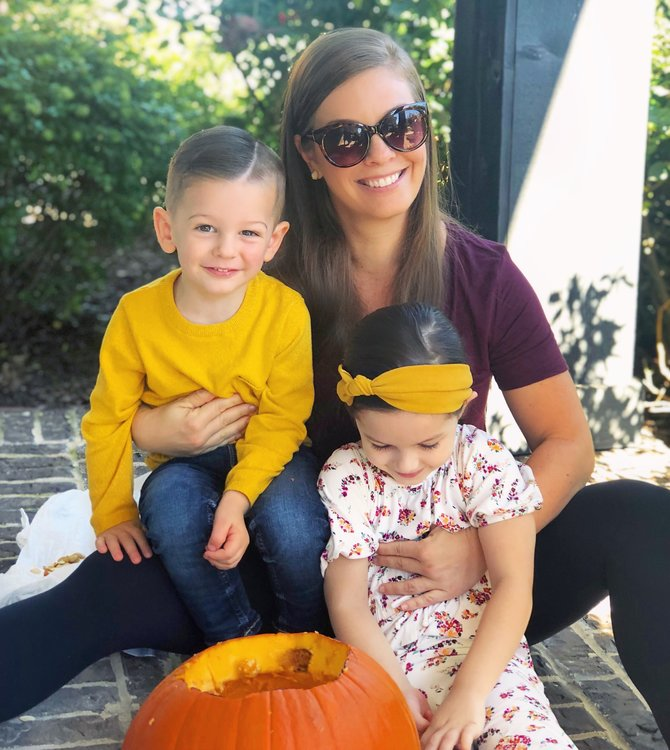 mother carving pumpkins with two toddlers