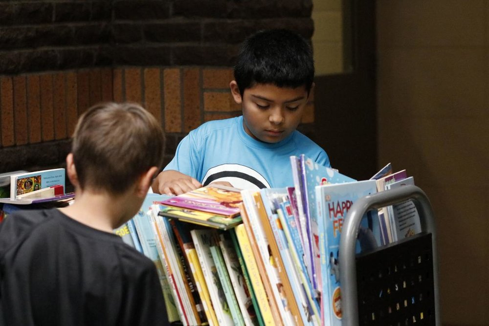 Hoover Elementary first graders Christian Martinez, in back, and Ethan Michael, front, skim through a selection of books to find their choices. Photo by Susan Payne