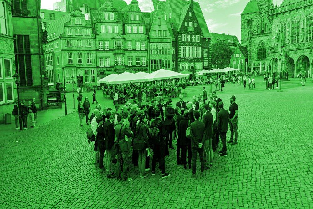 """Gemeinschaft - Hier geht es um die Schaffung eines Ortes für ein lebendiges, zukunftsweisendes Bremer Bürgertum als Fortsetzung des historischen Marktplatzes und als Agora des 21. Jahrhunderts. Leitidee ist """"Urbania – eine gemeinsame Idee von Stadt"""", vorgeschlagen wird ein marktplatzähnlicher Stadtraum mit freistehenden, öffentlichen Gebäuden. Inhaltlich geht es um die Schaffung einer Vielfalt gesellschaftlicher Nutzungen, die dem """"Public Interest"""" verpflichtet sind – von klassischem Gewerbe bis hin zu kulturellen, genossenschaftlichen oder politischen Aneignungen des geschaffenen Raums sowie einem Konferenzzentrum."""