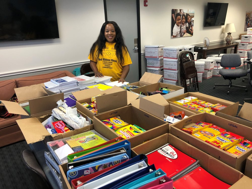 A Student Support Specialist picking up donated school supplies for their campus.