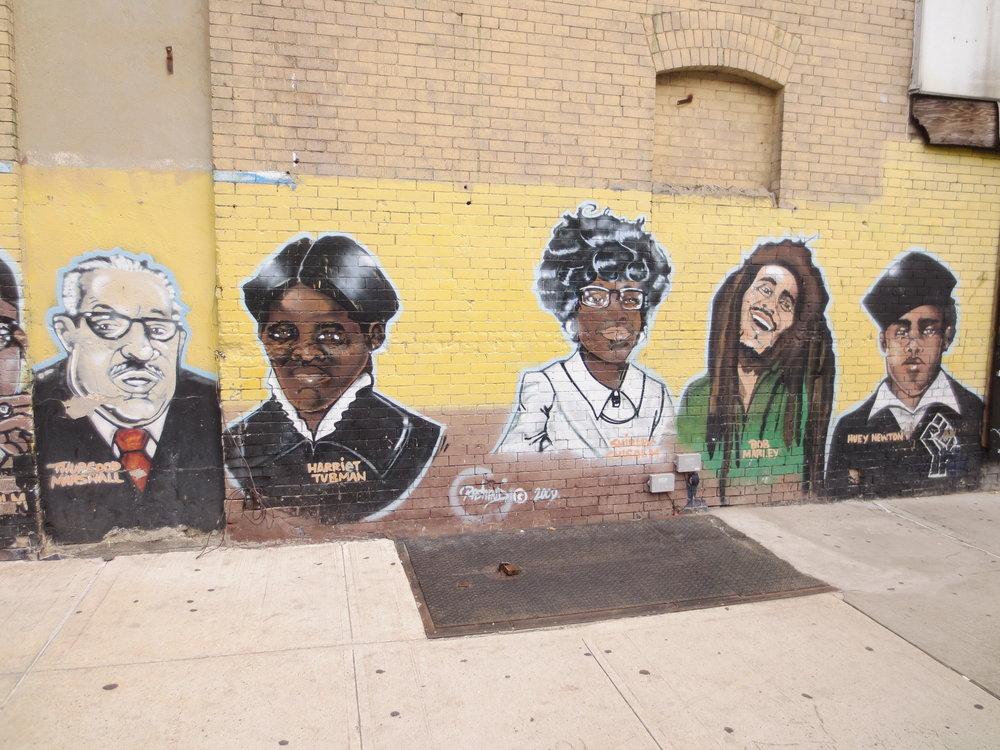 A long mural on Herkimer Place celebrating Black leaders.