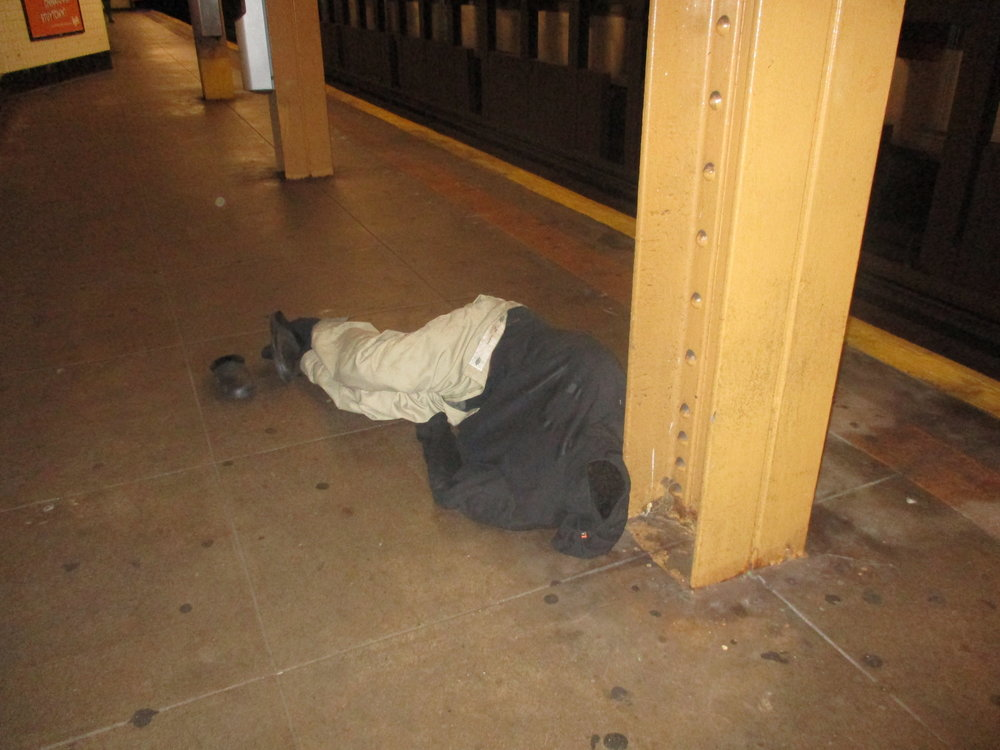 Man asleep on the platform of the Kingston Avenue subway stop. Didn't stir as the train came in the station maybe two feet away.