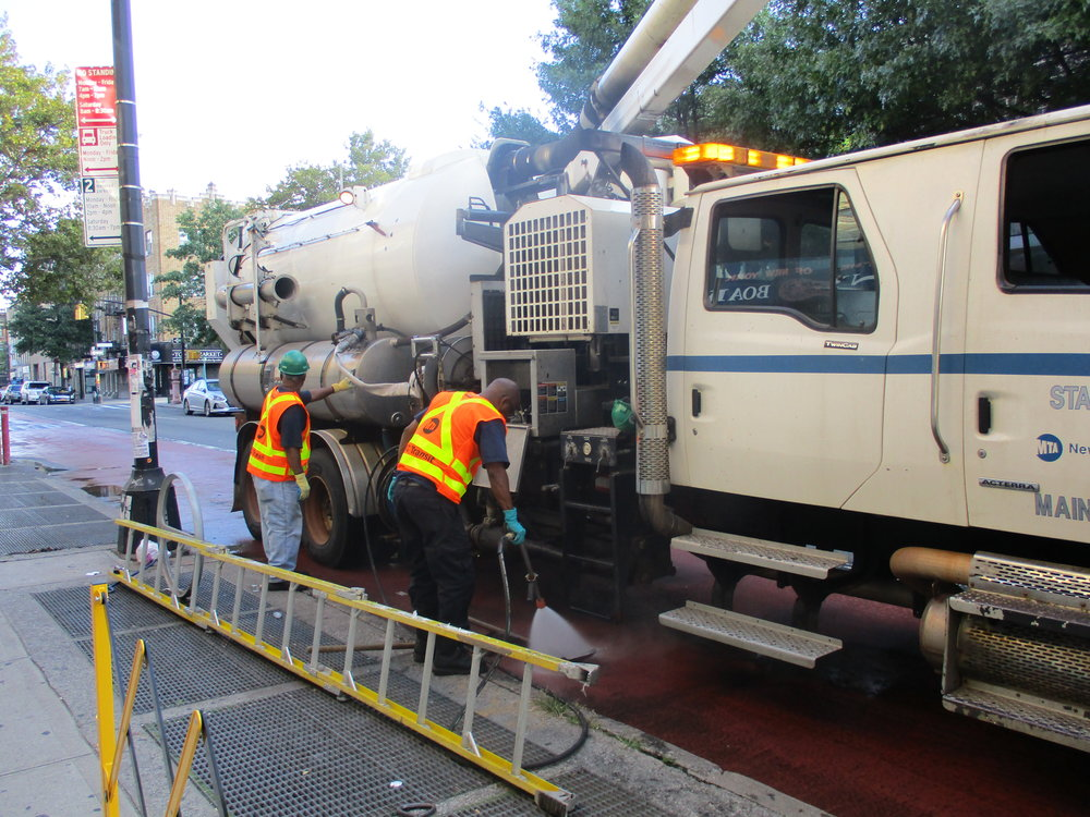 MTA workers cleaning out the air shafts on the no. 2 and 5 line on Nostrand Avenue one Saturday morning.