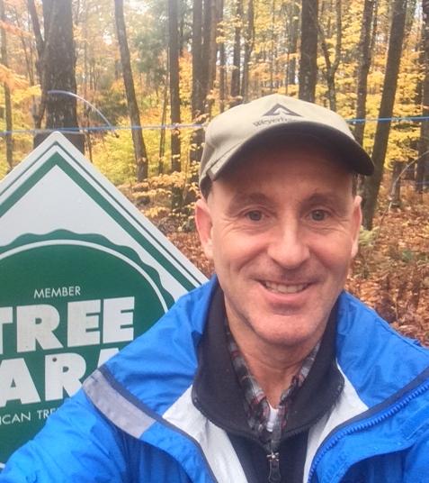 John at Tree Farm Sign.JPG