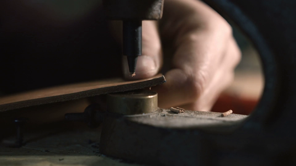 videoblocks-leather-craftsman-making-an-handmade-genuine-leather-bag-close-up-of-his-hands-using-an-hand-rivet-press-in-order-to-puncture-leather-4_rv7ipk2vz_thumbnail-full01.png